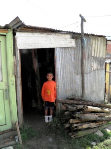 Juan Jesus' grandson stands in the doorway of his modest home