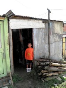 Juan Jesus' grandson stands in the doorway of his modest home
