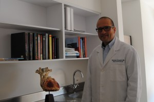 Dr. Franco stands near a collection of his textbooks