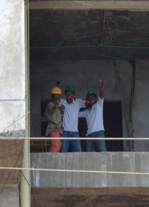 Construction workers on a high rise take a quick moment to say hello to yours truly.
