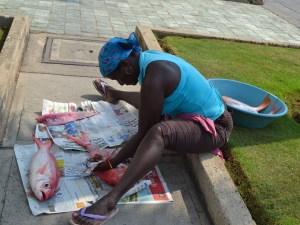 local woman prepares freshly caught fish