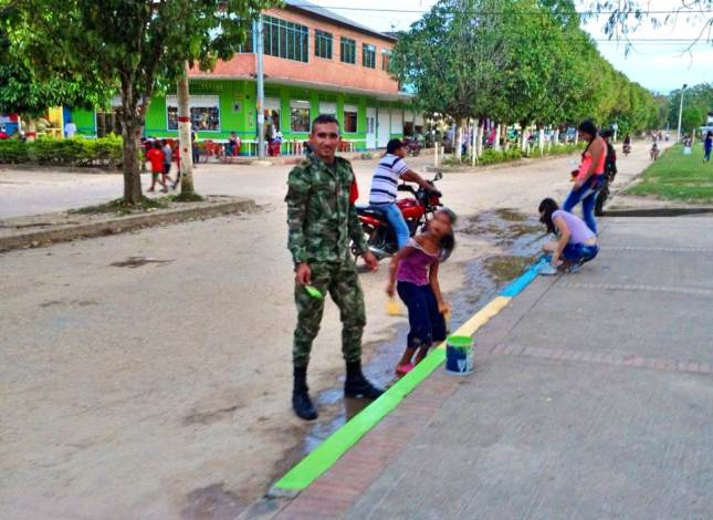 a soldier helps a young girl with the community painting project